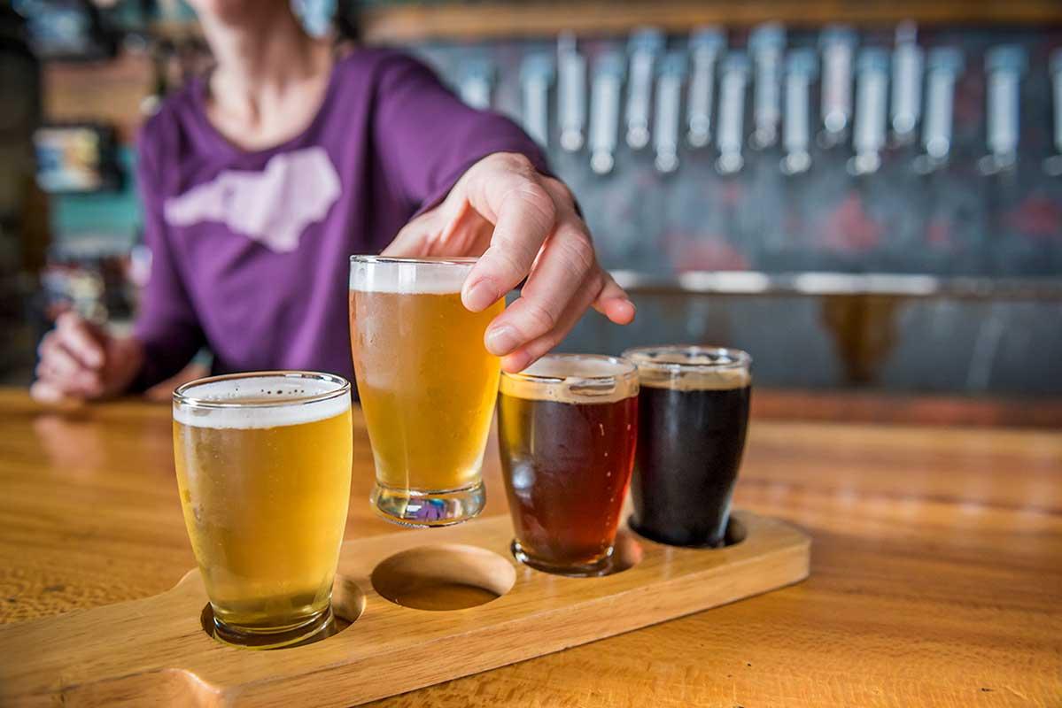 bartender placing beer in a flight server Asheville